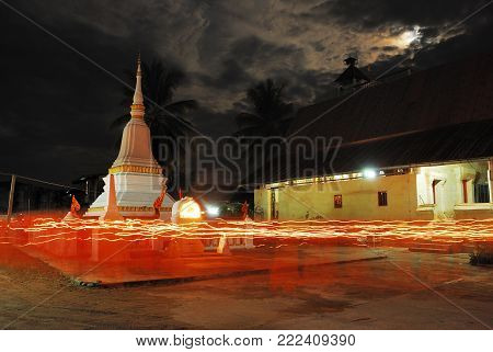 White pagoda in Thai Buddhist temple. Picture in the night time. Real people in triple circumambulation.