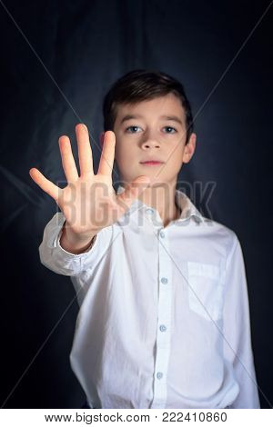 Stop a boy's hand a sign of discrimination or a violent violence symbol with a dark tone background. boy in white shirt shows palm stop sign. Focus on the hand.