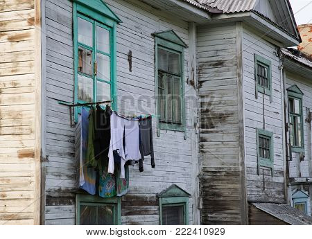 The linen is hung to dry out the window of an old wooden barrack