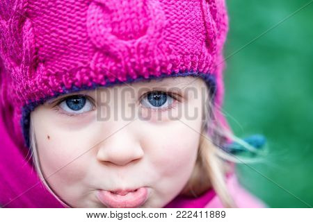 Portrait of little cute caucasian girl in pink knitted hat crying , being upset or lost in a forest or city park .