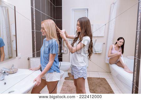 view of girl straightening friends hair in bathroom