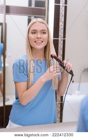 attractive girl straightening hair in bathroom with hair iron