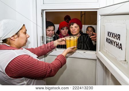 Berehove, Ukraine - December 14, 2017: Poor people receive a hot lunch in public kitchen for poor and homeless people.