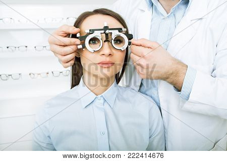 Man ophthalmologist examining patient woman with optometrist trial frame. female patient to check vision in ophthalmological clinic, face close-up