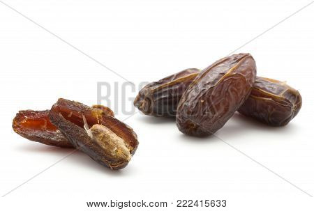 Date fruits Medjool variety isolated on white background three whole and two halves with a seed