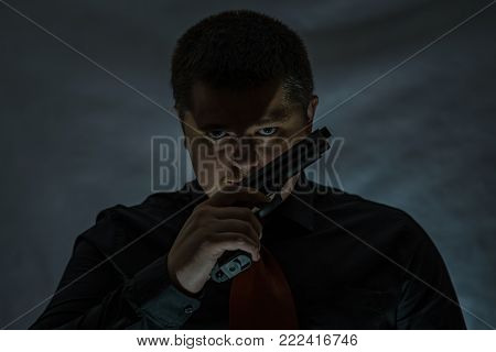 A criminal with a gun in his hand. The muzzle of the gun was pointed to the side. Mafia.