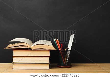 Educational background. Books pile and pencils against empty classroom blackboard for copy space. Back to school concept