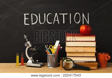 Educational background. Microscope, books pile, pencils, colorful liquids, magnifying glass, apple and coffee cup against classroom blackboard with written word education. Back to school concept