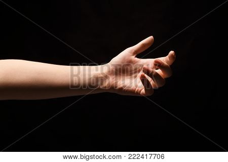 Tender female helping hand on black background, isolated. Woman stretching hand to show or ask for support and care, copy space, cutout