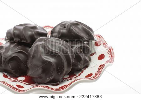 Dark chocolate-coated zefir on a porcelain plate isolated on white background