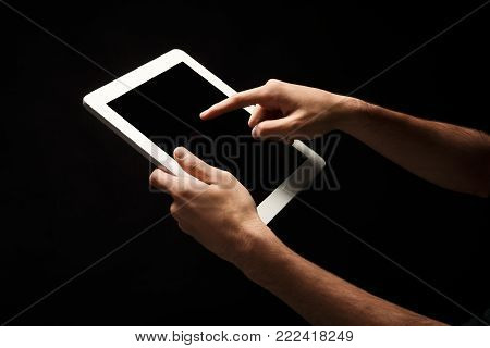 Male hands holding and pointing to blank screen of digital tablet. Caucasian man using device with emty screen, copy space for advertisement, isolated on black background