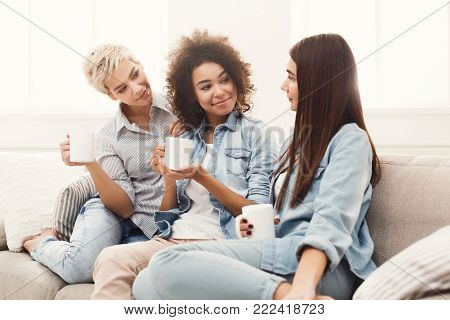 Three happy young female friends with coffee cups talking in living room at home, chatting about their life and relations, gossip and slumber party concept, copy space