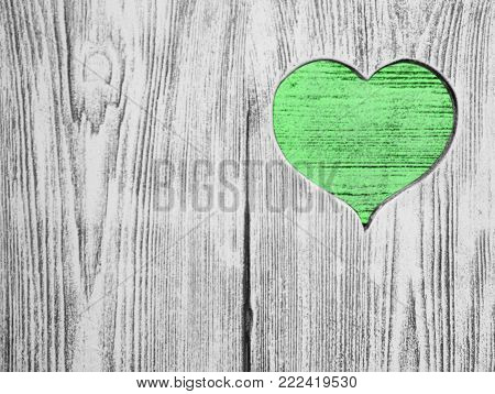 Green heart carved in a wooden board. Background. Postcard, valentine