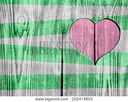 Red heart carved in a wooden board and green strips. Background. Postcard, valentine