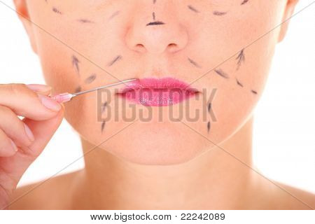 A close-up of female lips and a needle against white background