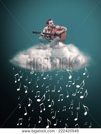Man playing guitar on a cloud and rains with music notes. The concept of composing music