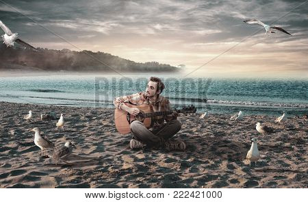 Young man playing guitar on the beach surrounded by seagulls.