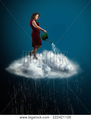 Woman in red dress standing over a cloud creating rain with watering can .