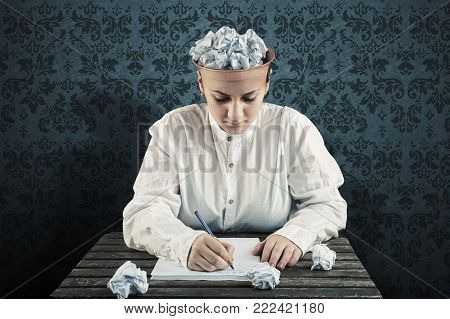 Woman with a crumpled paper in top of his head and writing on paper . Concept of ideas and creativity.