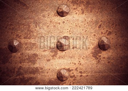 Brown grunge metal plate or armour texture with rivets as background poster