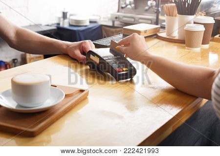 Unrecognizable barman giving POS terminal to customer with credit card at coffee shop counter. Small business, occupation people, payment and service concept, copy space
