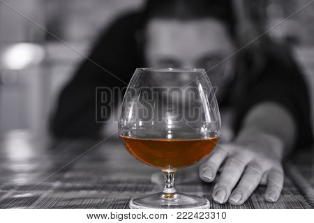 No focus. Female alcoholism. The hand reaches for a glass of cognac.