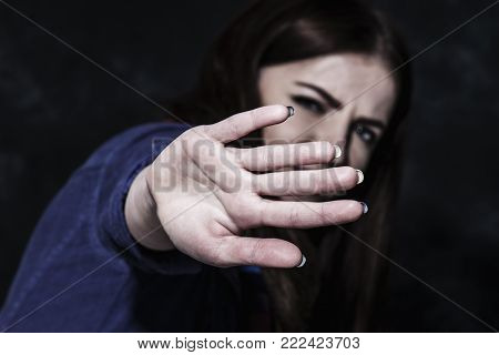 Portrait Of A Young Woman Looking In Fear With Her Hand In Front Of Face (gestures, Body Language, P