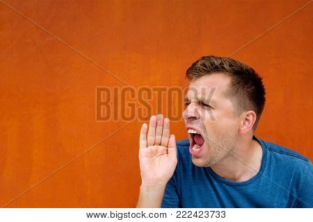 Young caucasian man yelling or shouting in anger on red background. Concept of negative emotion