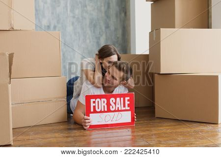 Young couple relaxing laughing after unpacking cartons from house move
