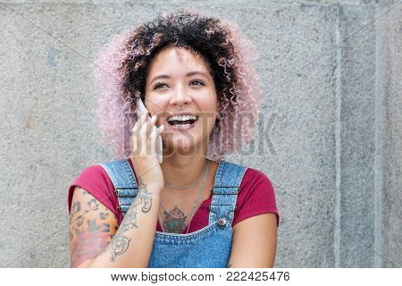 Beautiful punk girl with pink hair laughing at phone outdoors with copy space