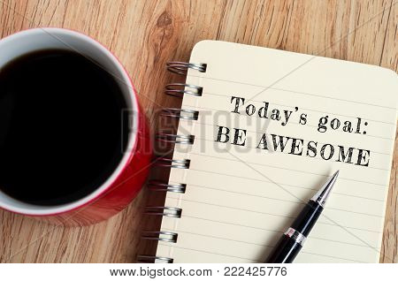 Today's goal - Be awesome text on notepad with pen and a cup of coffee, wooden background