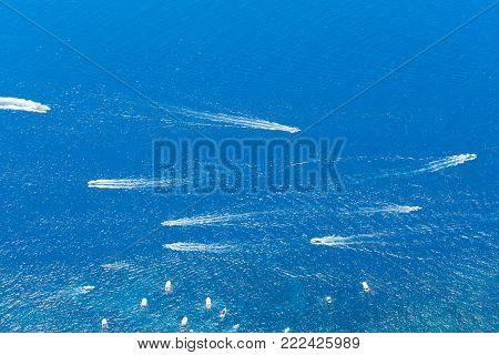 Tyrrhenian Sea waters glimming with sunlight and floating boats, aerial view , Capri island, Italy