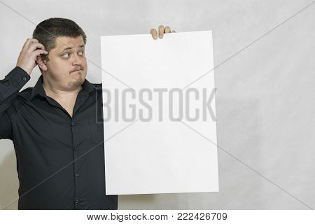 A man is holding an empty scoreboard or white square of paper. The white square is empty. On a white background. copyspace