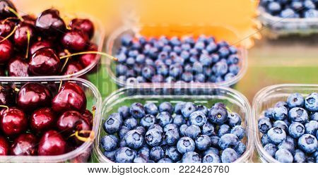 Various berries from a local farmer market.  Healthy local food market concept. Variety of berries in a box -  raspberry, strawberry, cherry