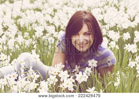 Young beautiful woman smelling daffodils. Nostalgic filter. Beauty and nature.