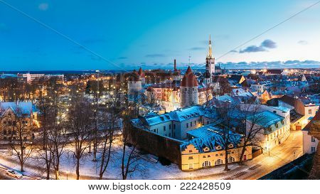 Tallinn, Estonia. Panorama Of Old Part Of Traditional Medieval Houses, Old Narrow Streets And Ancient Towers With Fortification Walls In Evening, Night Illumination. Blue Sky Background With Copyspace