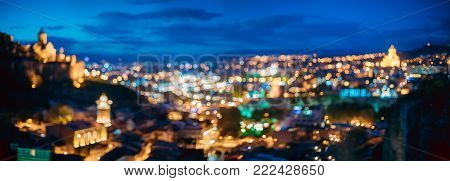 Tbilisi, Georgia. Abstract Bokeh Backdrop Of Panorama Of Narikala Fortress, Sameba Holy Trinity Cathedral In Evening Night Illumination. Real Blurred Boke Background With Defocused Lights