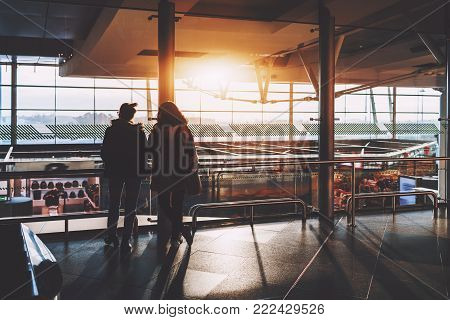 View from behind of two women in warm clothes standing in modern airport terminal near glass fence over duty-free zone and looking at parked airplanes and runway behind facade in defocused background