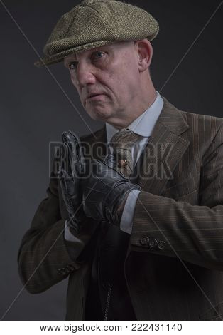 Vertical portrait of a angry gangster with his fists up ready to fight
