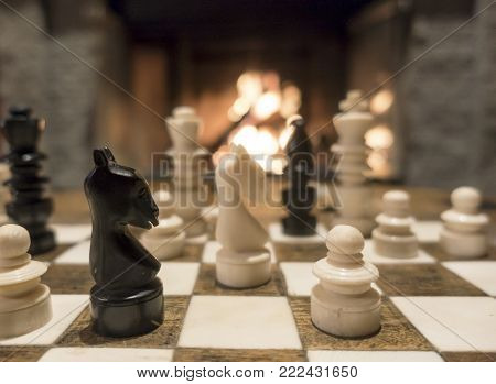 Picture of chess pieces on a chess board in front of fireplace.