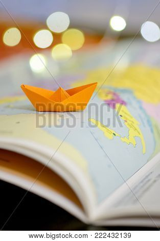 Paper boat on a atlas book map of the world