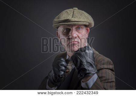 Portrait of a mature gangster with his fists up ready to punch, taken with copy space