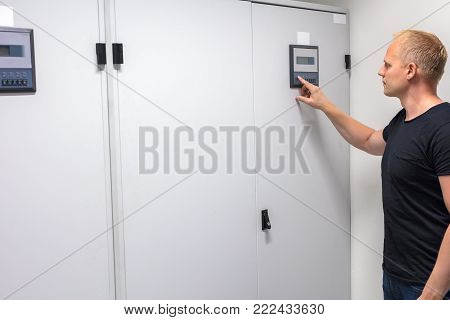 Mid adult male technician pressing button on control panel to adjust air conditioner in datacenter