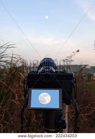 A camera on a tripod taking photo of the rising full moon in a cloudy sky,Digital camera on camera tripod taking a photo of moon at night