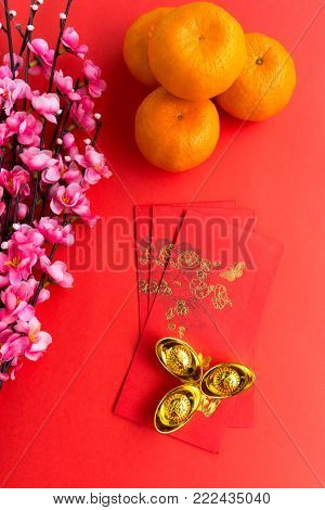 Chinese New Year background concept - Chinese New Year Background Ornaments, Mandarin Orange, Red Envelopes, Plum Flowers and Gold Ingots with Chinese Character Happiness and Prosperity.