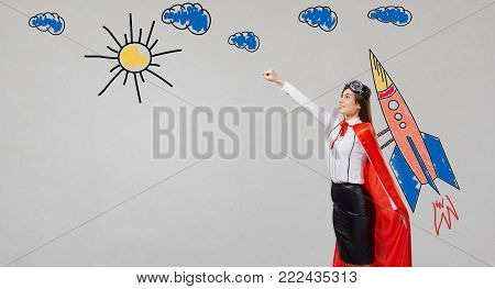 The concept of a successful superwoman. A girl in a superhero costume with a painted missile.