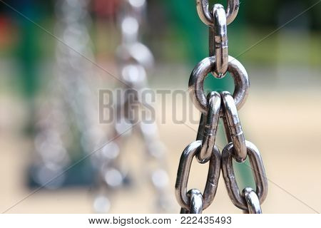 Chain Links closeup of a metal steel chain link segment from a children's swing set. Outdoors