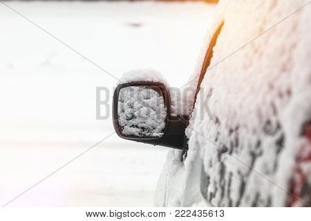 The Car Is All Covered With Snow. Snow On Rearview Mirror. Concept Of Driving In Winter Time With Sn