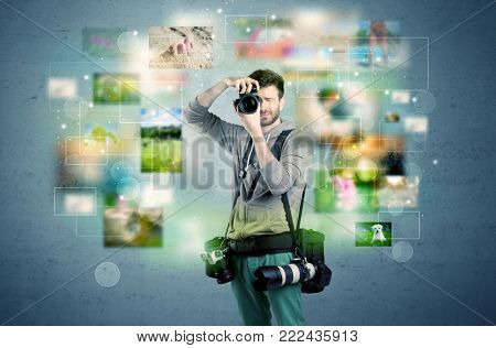 A young amateur photographer with professional camera equipment taking picture in front of blue wall full of faded pictures and glowing lights concept