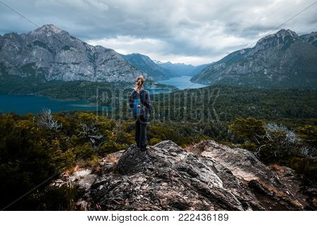 Woman hiker stands and enjoys valley view from the viewpoint. Patagonia, Argentina